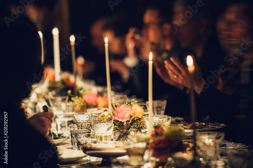 People enjoy a family dinner with candles Fotobehang