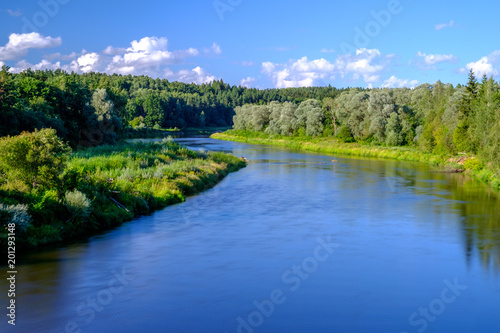 Fotografie, Obraz  Bank of Gauja River in Latvia with blue sky and white clouds reflecting in water