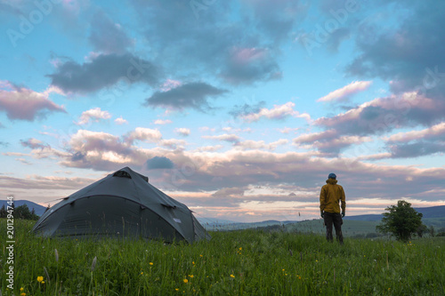 Canvas Prints Camping man standing next to a tent pitced on a meadow, looking at a clouds during sunset