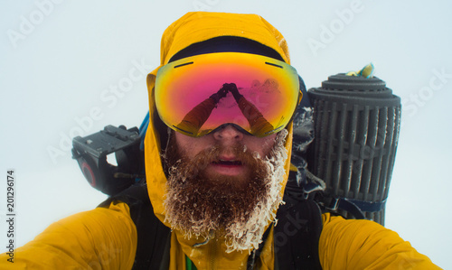 bearded male mountaineer takes a selfie in a winter whiteout conditions, reflect Fototapeta