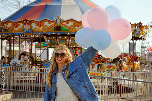 Photo  Beautiful young woman with balloons in the amusement park