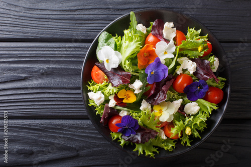 Photo Stands Ready meals Fresh organic salad from edible flowers with lettuce, tomatoes and cream cheese close-up. Horizontal top view