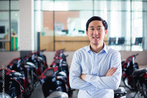 Young Asian man in business office outfit posing in front of many motorcycles in the company office in the background.