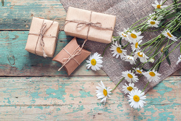 Rural background with daisies and gift boxes.