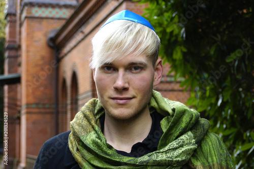 Photo Junger Mann mit Kippa vor einer Synagoge