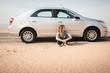 Girl have rest near car in desert
