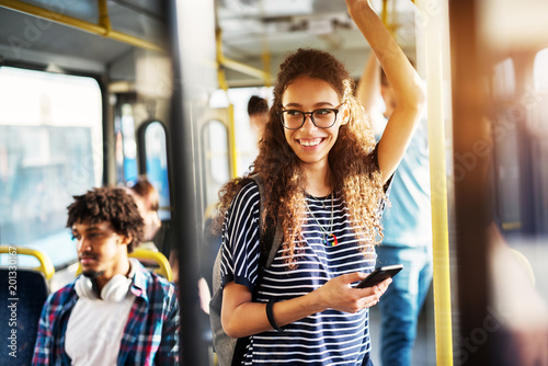 Young gorgeous cheerful woman is standing on the bus using the phone and smiling Canvas Print