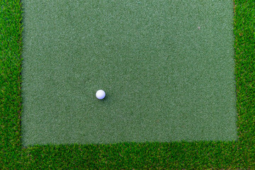 Golf ball on artificial green grass textures background and copy space.