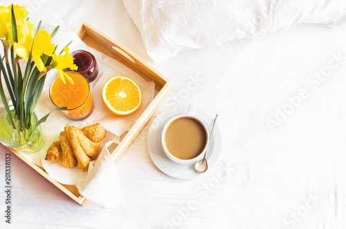 Fotografie, Obraz Morning breakfast in bed wooden tray with a cup of coffee croissant orange juice fresh orange jam bouquet of flowers daffodils