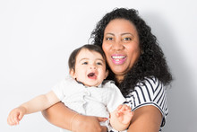 American Black Young Mother Plays With A Baby. A Woman Plays With Mixed Race Child Eight Months Of Age