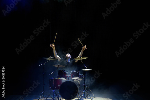 Photo Drummer in a cap and headphones plays drums at a concert under white light in a