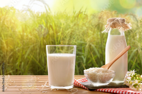 Composition with rice drink on wooden table in the field