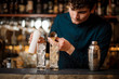 barman begins preparing two alcoholic cocktails