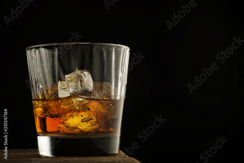 Foto op Plexiglas Bar Glass of scotch whiskey and ice on a wooden table.