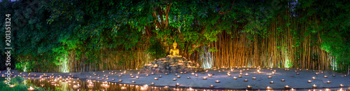 La pose en embrasure Buddha monks sitting meditate with many candle in Thai temple at night , Chiangmai ,Thailand,