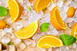 Mixture of sliced fresh citrus fruits, orange, lime, lemon and kumquat for squeezing juice on ice and wooden table