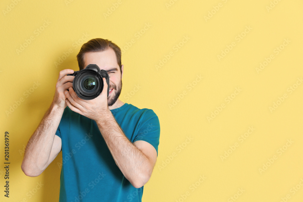 Fototapety, obrazy: Young photographer with professional camera on color background