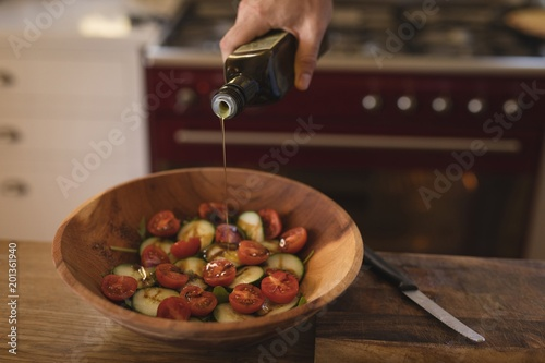 Man pouring edible oil on vegetable in kitchen