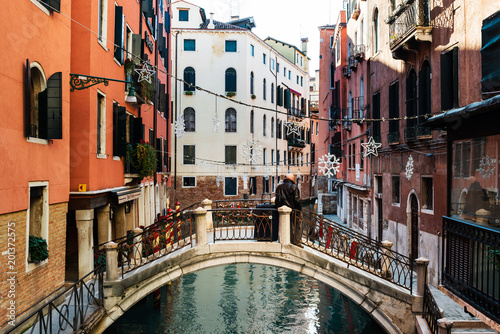 Fototapety, obrazy: VENICE, ITALY - December 21, 2017 : Tourists foot Street in Venice. its entirety is listed as a World Heritage Site, along with its lagoon. VENICE, ITALY.