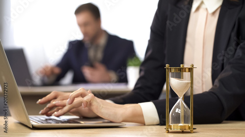 Businesswoman working on computer, hourglass trickling, outcome anticipation Wallpaper Mural