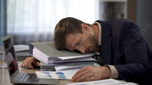 Photo Depressed businessman lying on pile of folders, deadline pressure, exhaustion