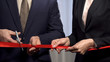 Business people cutting red ribbon with scissors, start-up and collaboration