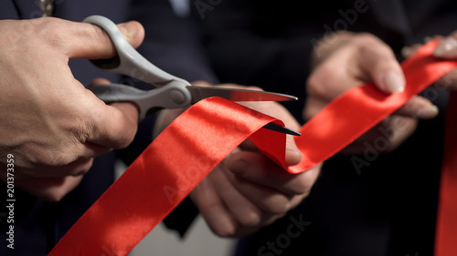 Business people hands cutting red ribbon close-up, new project, opening ceremony Fototapet