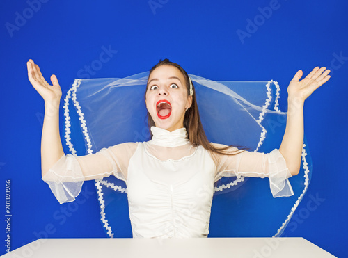Fotografija  pretty jung funny bride in white fop spread her arms on both sides of the excite