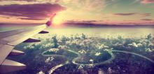 Concepto De Viaje En Avión .Volando Sobre La Ciudad Hacia El Destino. Paisaje Al Atardecer Sobre Las Nubes.