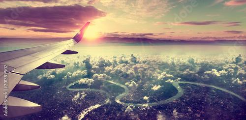 Spoed Foto op Canvas Vliegtuig Concepto de viaje en avión .Volando sobre la ciudad hacia el destino. Paisaje al atardecer sobre las nubes.