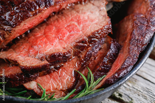 Garden Poster Steakhouse Close up of a beef steak medium rare with baked garlic and rosemary in a black cast pan over rustic table.