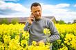 canvas print picture - Lnadwirt im blühenden Rapsfeld telefoniert mit seinem Pflanzenbauberater