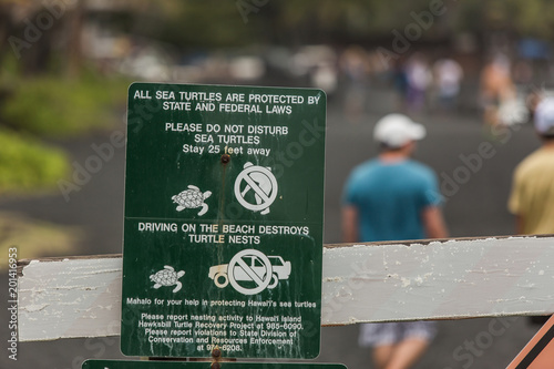 Foto op Canvas Natuur Signs warn against disturbing turtles at Punaluu Black Sand Beach Park, while in the background visitors tour the shore on the Big Island of Hawaii.