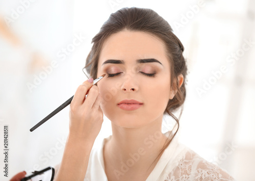 Fotografía  Professional makeup artist working with young woman in salon