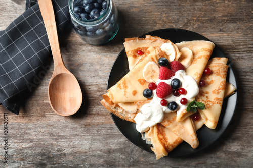 Papiers peints Plat cuisine Thin pancakes with berries and cream on plate, top view