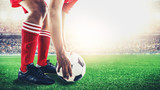 Fototapeta Sport - red team soccer footballer get the ball to free kick or penalty kick during match in the stadium