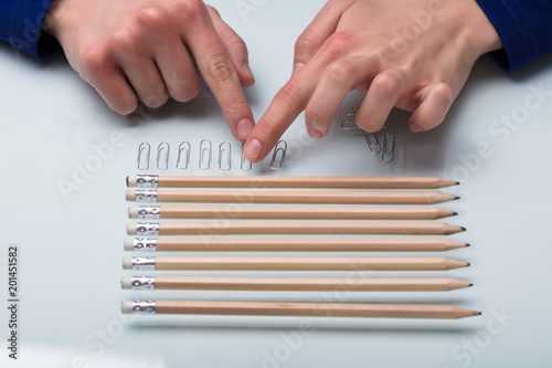 Human Hand Arranging Paper Clips In A Row Fototapet