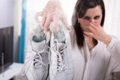 Fototapeta Woman Holding Her Smelling Exercise Shoe obraz