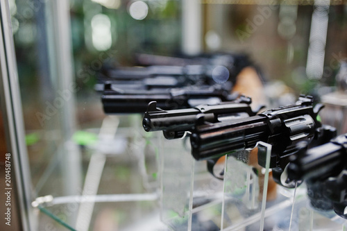 Fotografie, Obraz  Different guns and revolvers on shelves store weapons on shop center