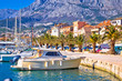 Colorful Makarska boats and waterfront under Biokovo mountain view