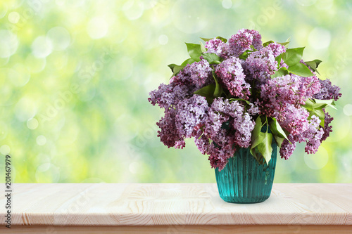 Keuken foto achterwand Lilac Bouquet of lilacs on a wooden table. Flowers in a vase.