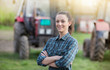 Leinwandbild Motiv Farmer woman with tractors on farmland