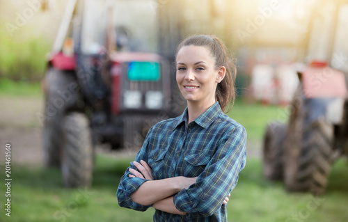 Fotografia  Farmer woman with tractors on farmland
