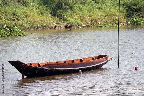 Obraz na plátně Sampan boat parked in the middle of the river