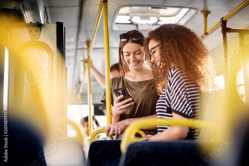 Fotografía Two cheerful pretty young women are standing in a bus and looking at the phone and smiling while waiting for a bus to take them to their destination