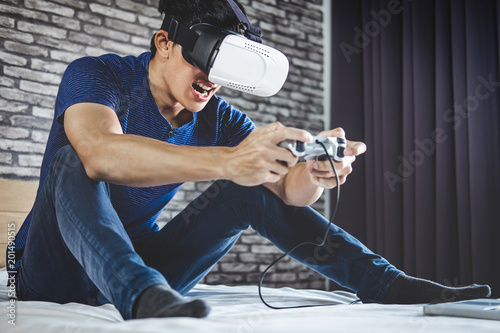 e1d799d9b18 Young man have fun on bedroom in virtual reality headset or 3d glasses  playing video game