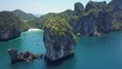 AERIAL: Giant limestone cliffs overgrown with exotic greenery protect sandy beach and boats in calm bay. Flying around a lonely karst islet reveals a popular tropical beach and gorgeous emerald sea.
