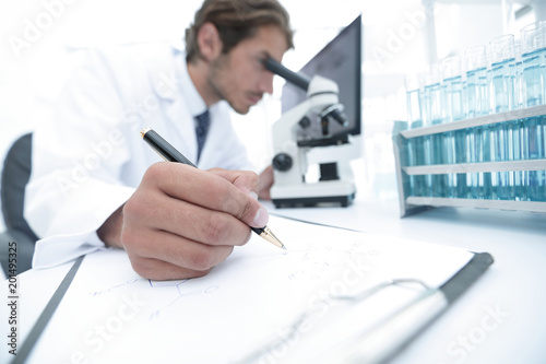 Fotografia  scientist makes a note of experiment in the laboratory