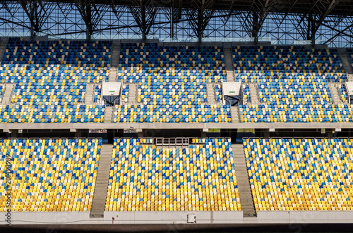 Papiers peints Stade de football Blurred sitting fans colored plastic chairs at the football stadium background. Empty stadium football field green grass for soccer athletics arena.