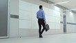 Businessman walking through hallway with briefcase and carrying personal belongings to new office